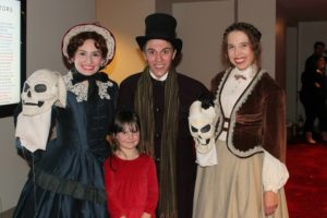 Members of A Christmas Carol cast with a young fan.