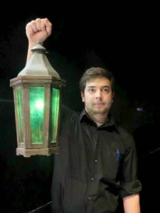 A Hartford Stage staff member holds a green lamp aloft to warn of potential trigger content.